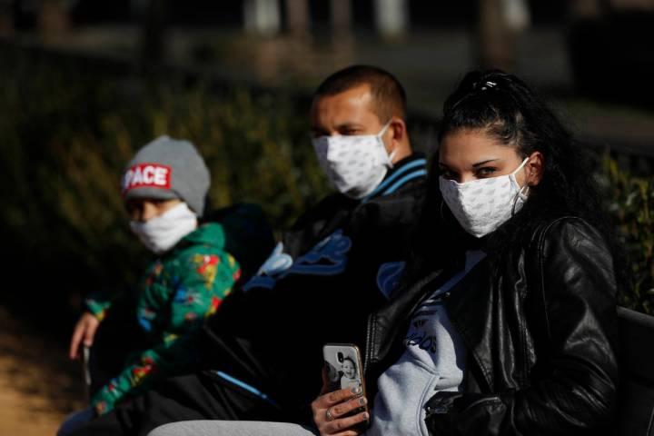 Archivo.- Una familia con cubrebocas faciales disfruta de un día soleado en un patio de recreo ...