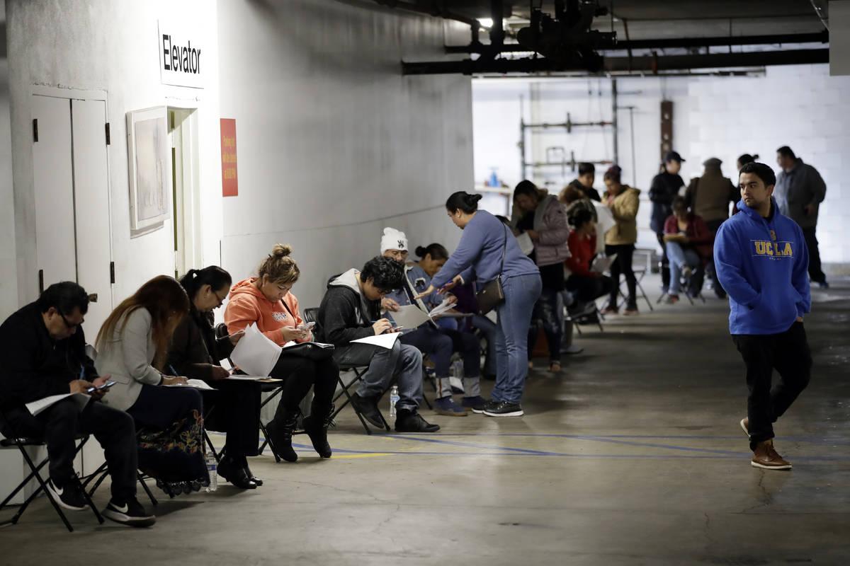 Trabajadores de hostelería sindicalizados hacen fila en un garaje para solicitar prestaciones ...