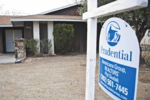 Un letrero de una agencia inmobiliaria se muestra fuera de una casa embargada en un vecindario ...