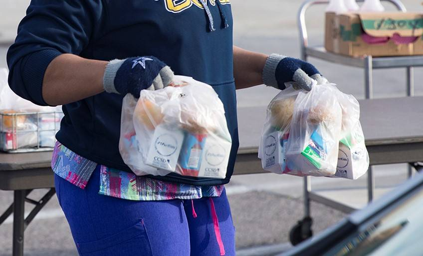 Un trabajador reparte paquetes de desayuno y almuerzo a las familias en una escuela en marzo de ...