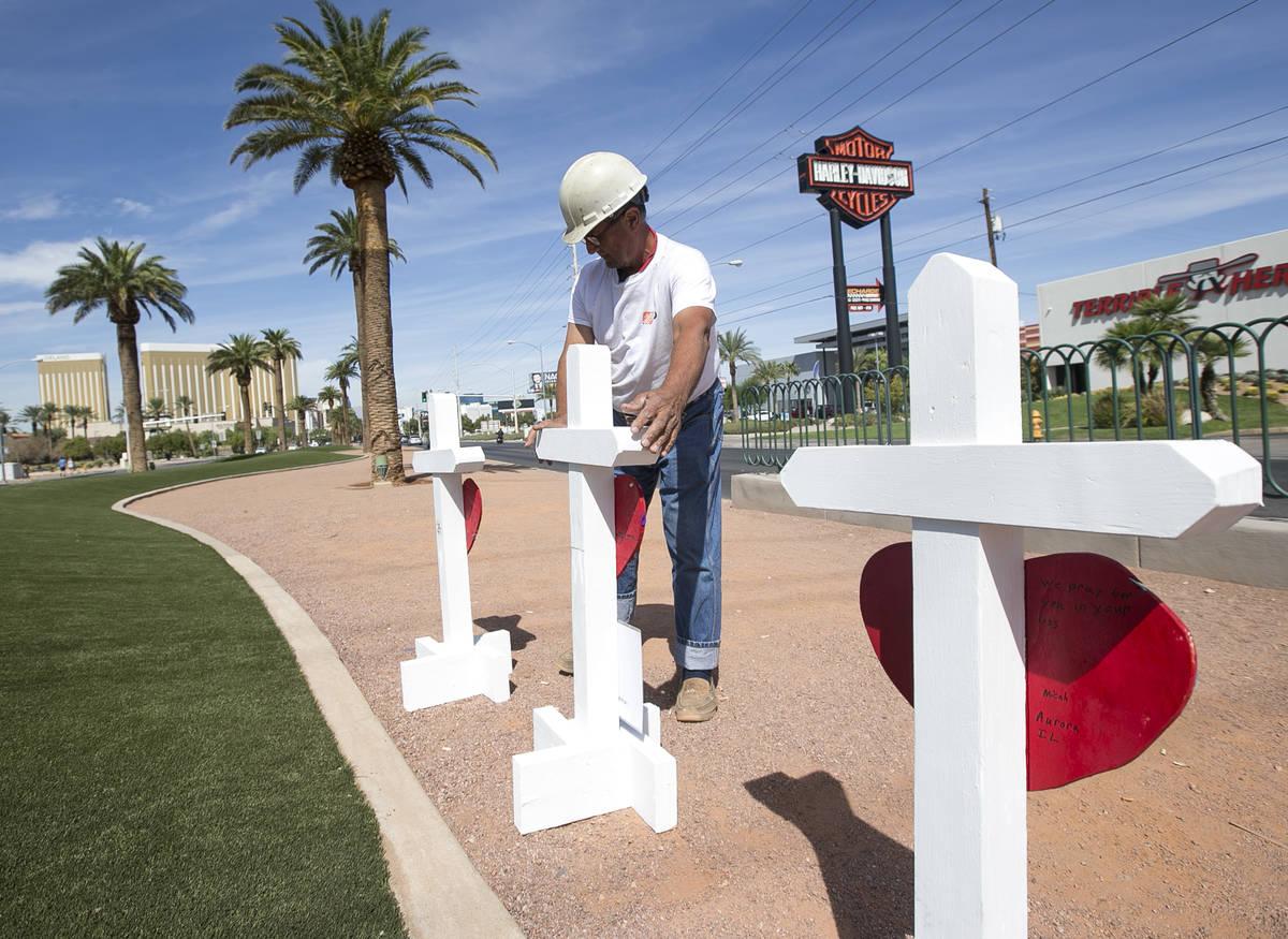 """Greg Zanis, de Aurora, Ill., lleva una de las 58 cruces que colocó cerca del letrero """"Welcome ..."""