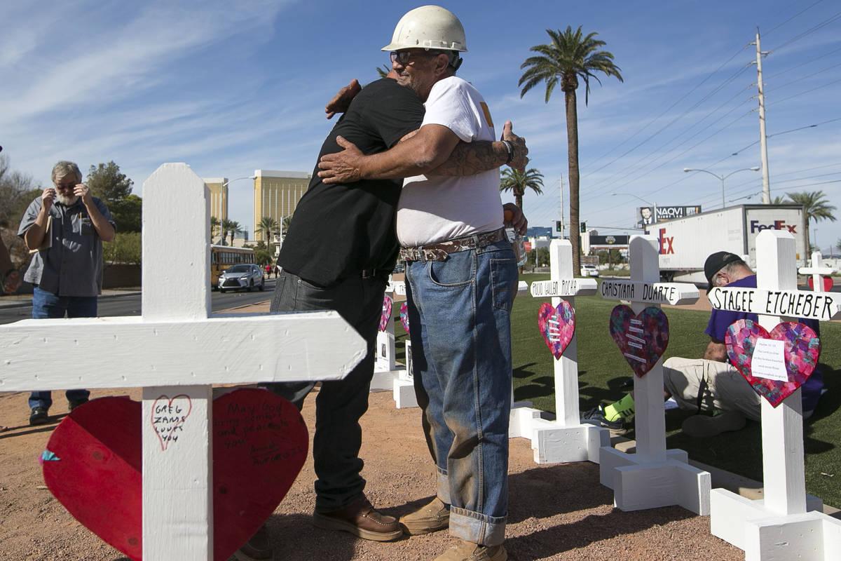 El fabricante de cruces Greg Zanis, derecha, recibe un abrazo de Mike Warino, hermano de la ví ...
