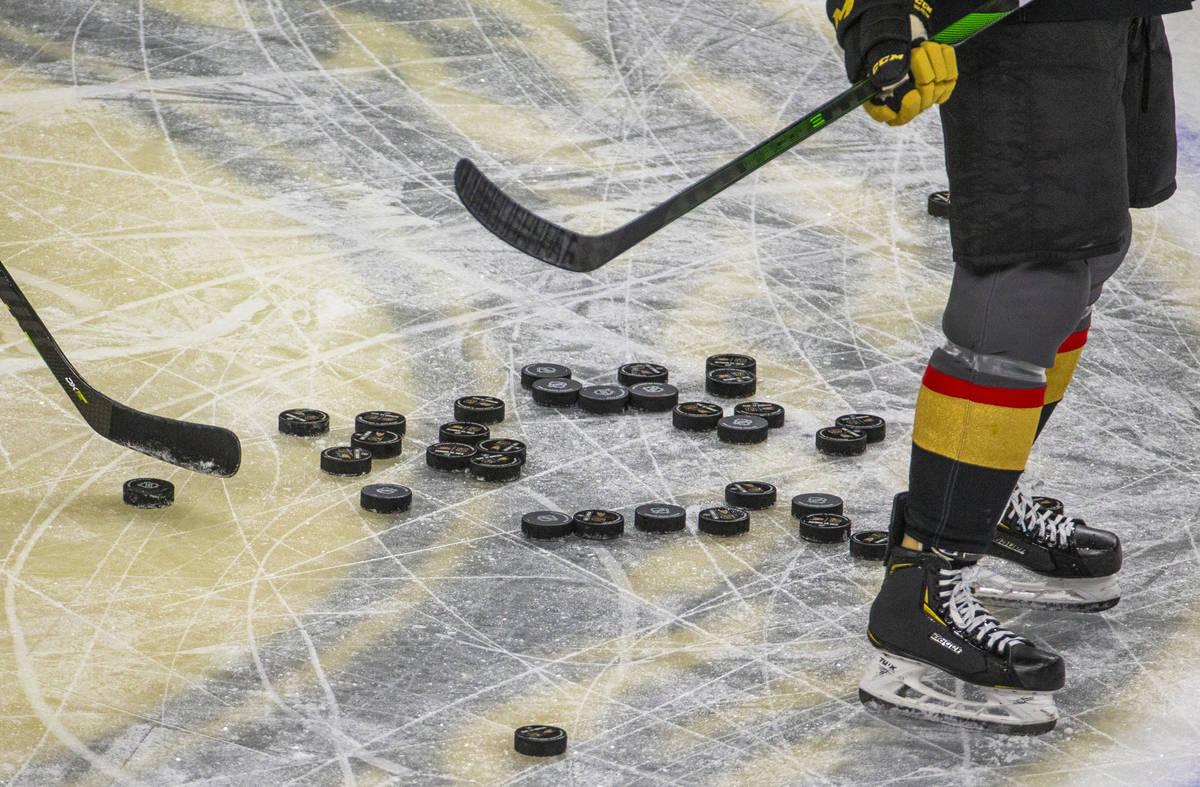 Los pucks se amontonan en el hielo mientras los Golden Knights de Las Vegas calientan antes del ...