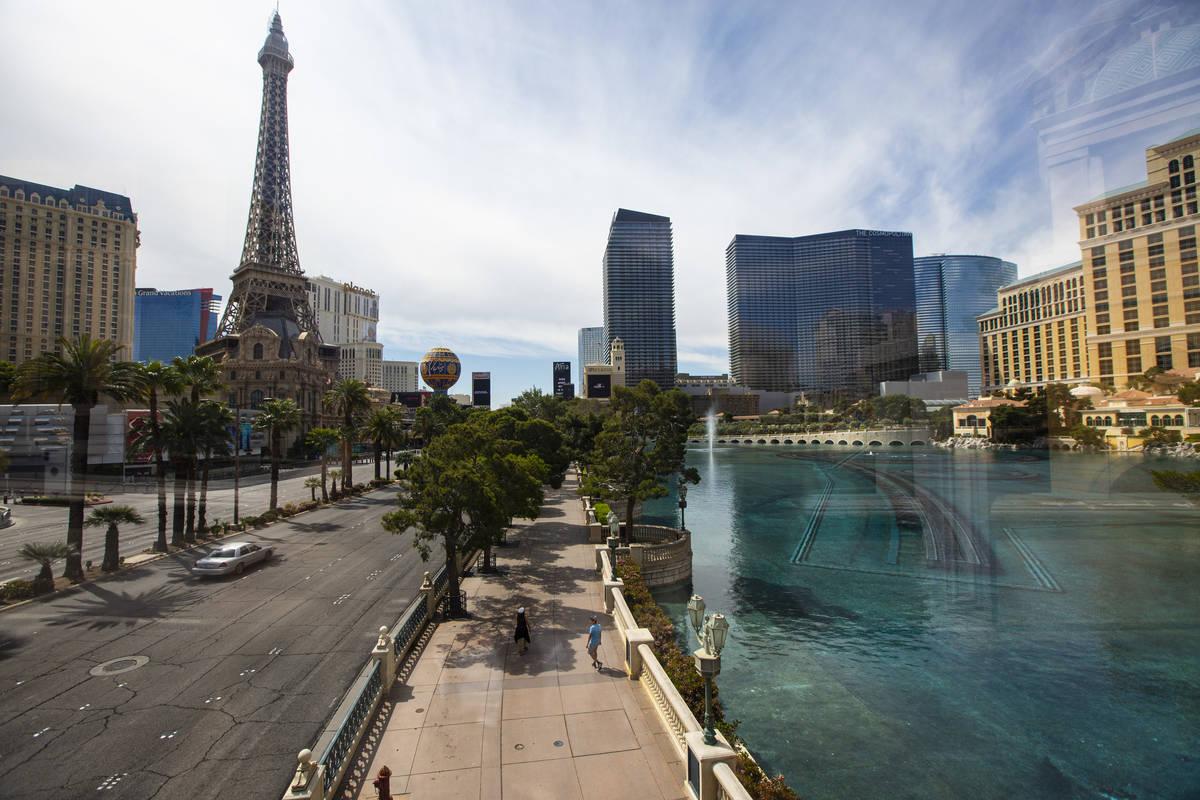 La gente pasa por el Bellagio en el Strip de Las Vegas el jueves, 16 de abril de 2020. (Chase S ...