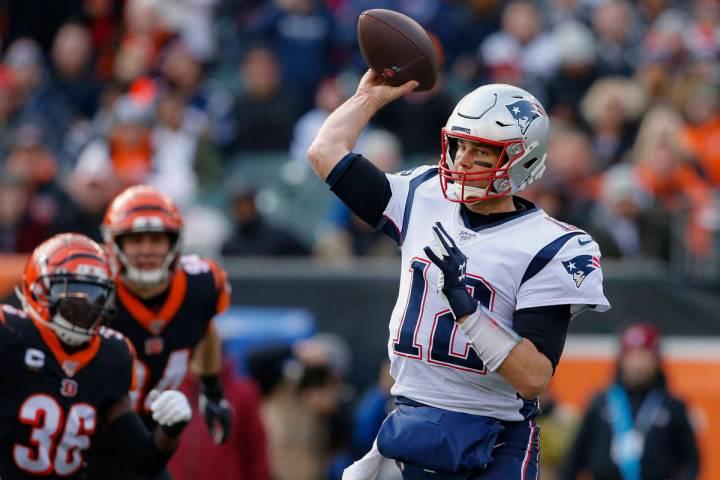El mariscal de campo de los New England Patriots, Tom Brady (12), pasa el balón en la primera ...