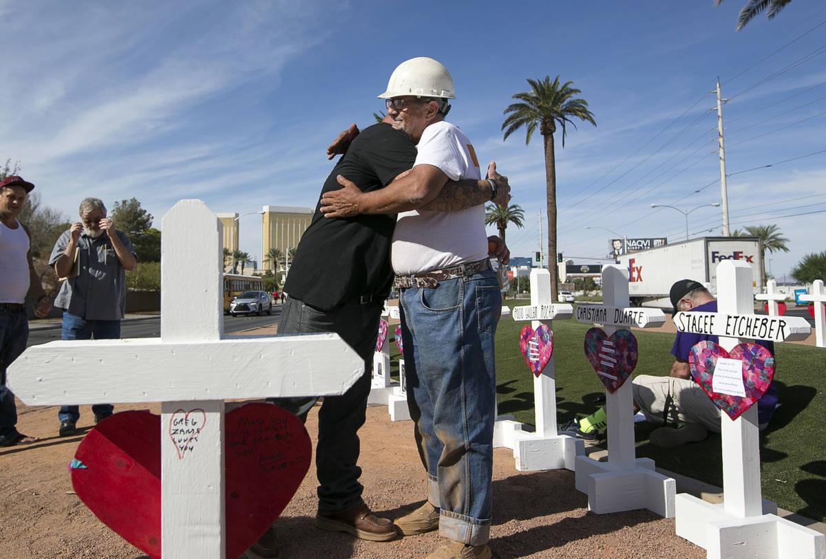 El creador de cruces, Greg Zanis, derecha, recibe un abrazo de Mike Warino, hermano de la víct ...