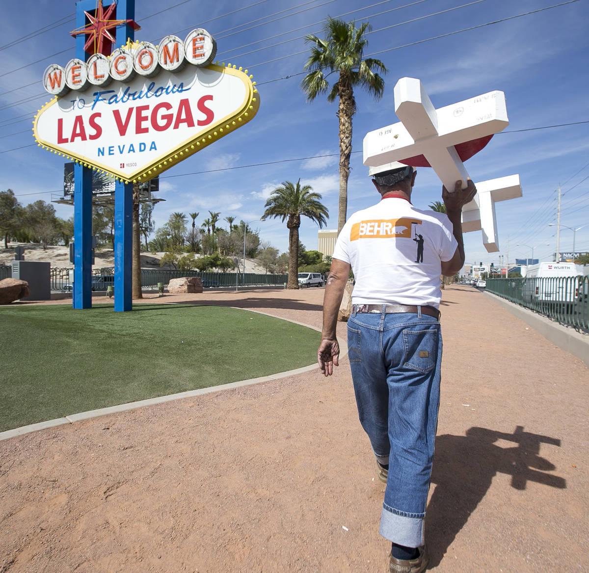"""Greg Zanis, de Aurora, Ill., carga una de las 58 cruces que colocó cerca del letrero """"Welcome ..."""