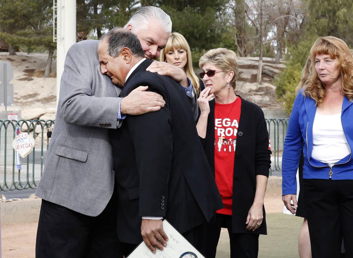 El entonces comisionado del Condado Clark, Steve Sisolak, a la izquierda, abraza a Greg Zanis d ...
