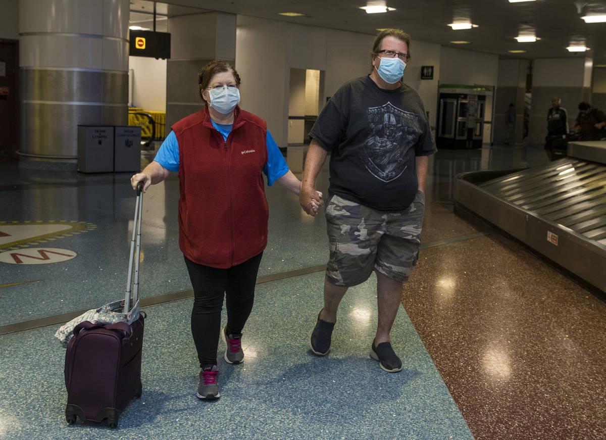Susan Yowell y su marido Jack se toman de la mano al salir de la Terminal 1 de reclamo de equip ...