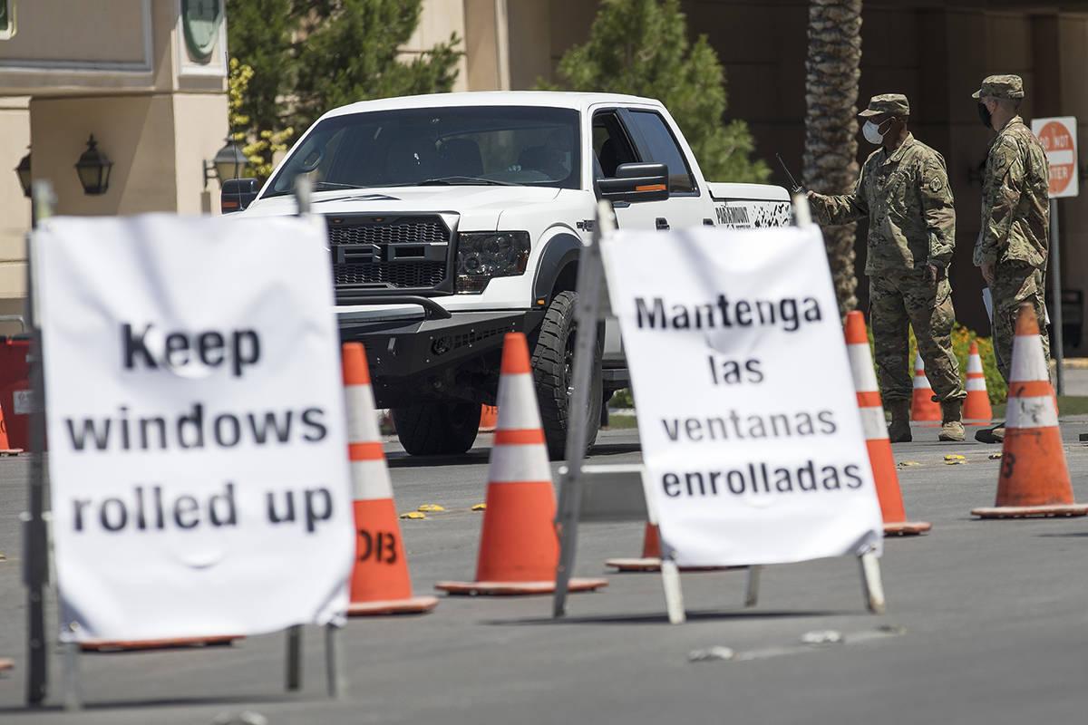 Miembros de la Guardia Nacional de Nevada dirigen a una persona en la estación de pruebas driv ...
