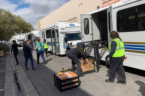 Trabajadores (y voluntarios de Three Square Foiod Bank) cargan víveres en vehículos de paratr ...