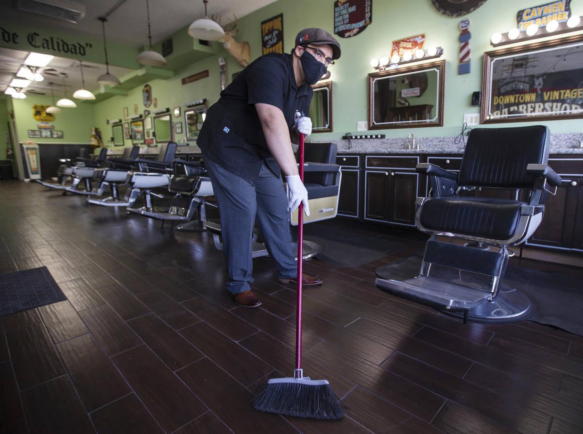 Jorge Reyes, propietario de Downtown Vintage Barbershop, limpia su tienda en preparación para ...
