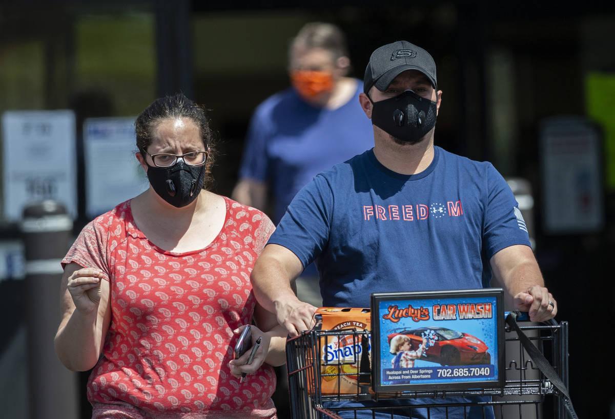 Compradores portan cubrebocas al salir de Albertsons al noroeste de Las Vegas el jueves, 7 de m ...
