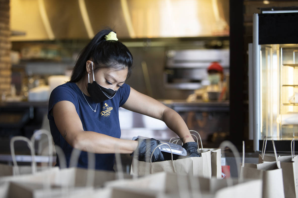Juliana Asa llena un pedido para llevar en Nora's Italian Cuisine el miércoles, 6 de mayo de 2 ...