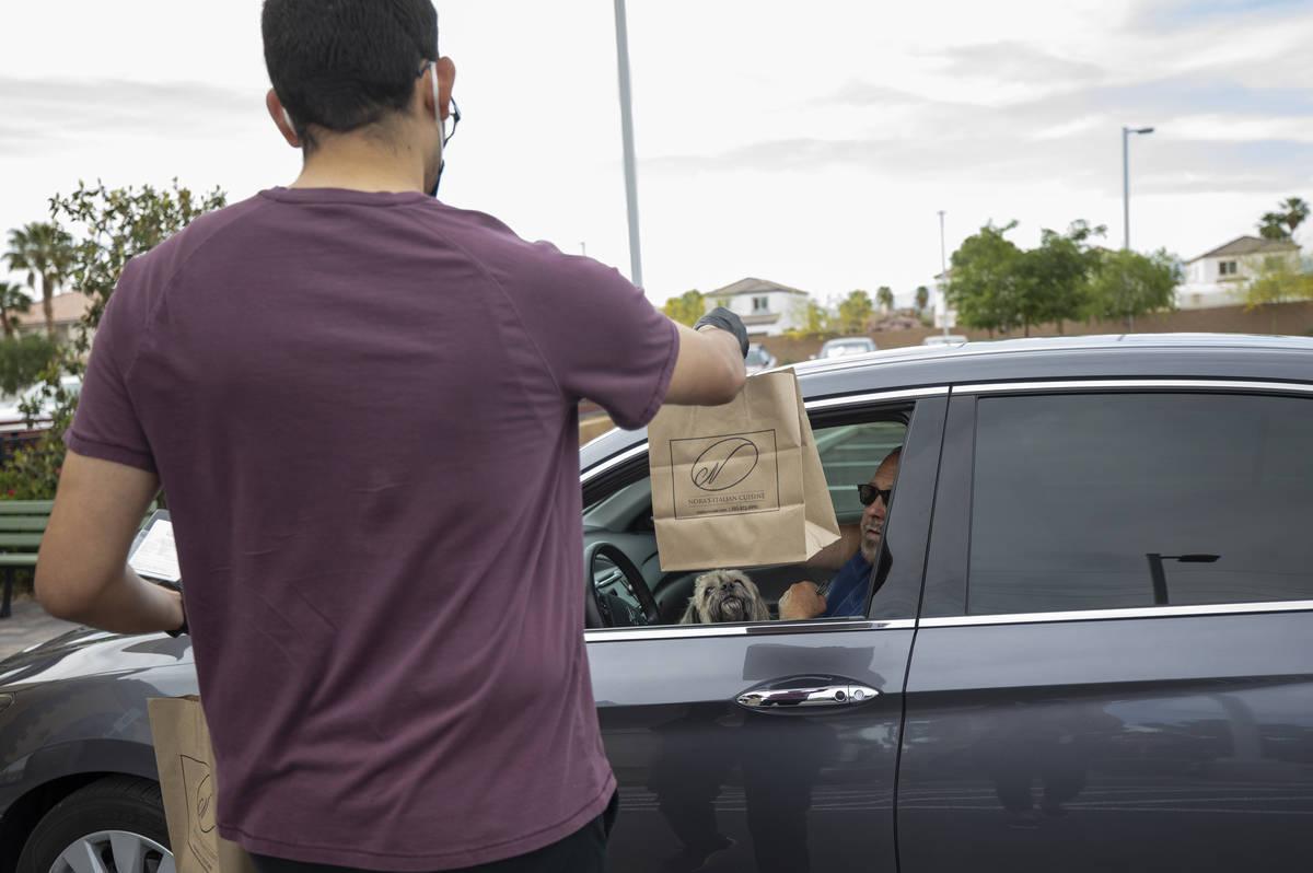 Anthony Campos le entrega a Gil Jordan su orden en Nora's Italian Cuisine el miércoles, 6 de m ...