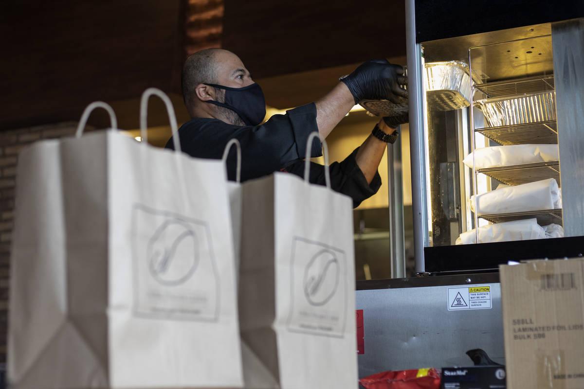 Misael Macías pone comidas calientes en una caja caliente mientras que los pedidos de recogida ...