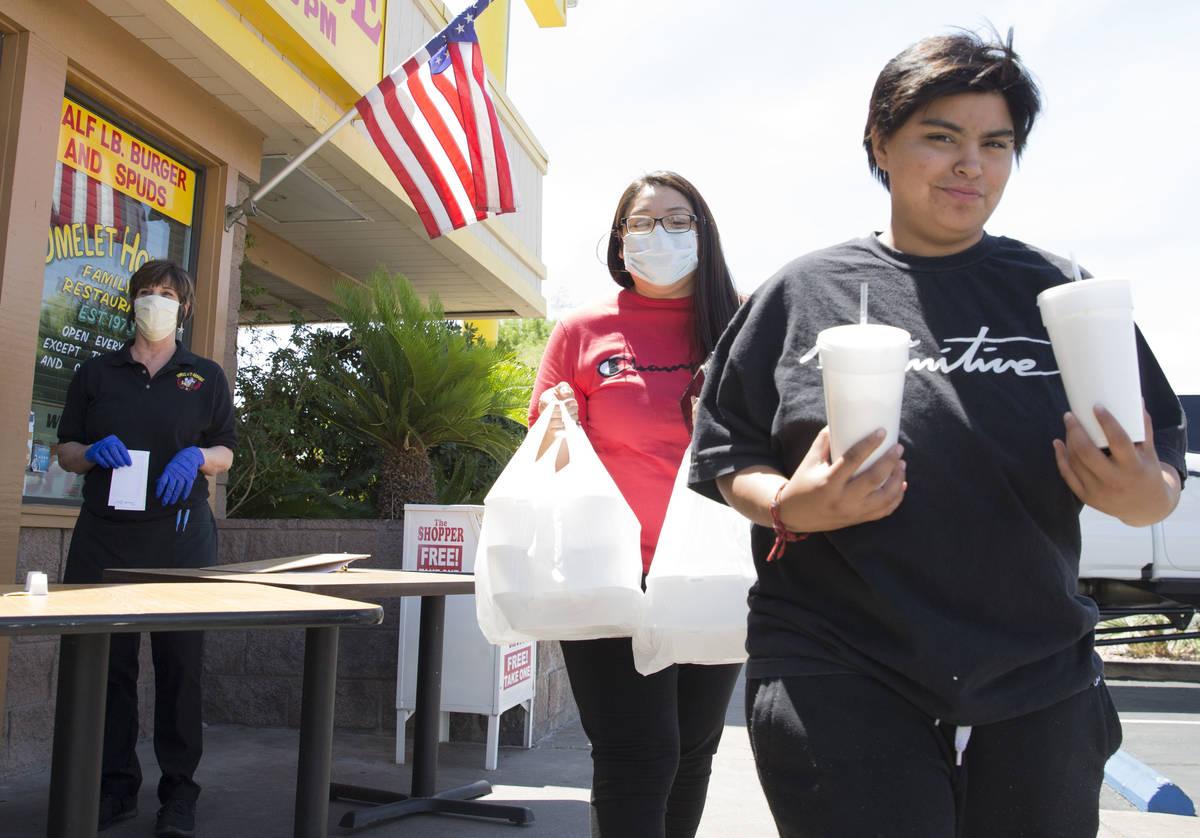 Amanda Sánchez, centro, y su hija Destiny Torres, recogen su pedido en una zona de recogida en ...