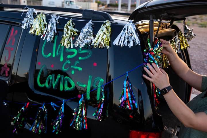 Vanessa Gálvez coloca las decoraciones antes del comienzo del desfile de Desert Oasis High Sch ...