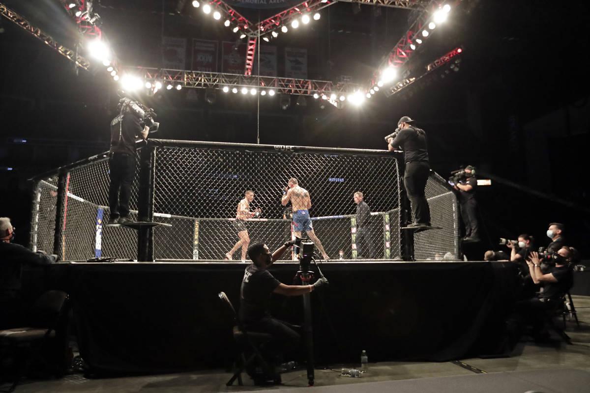 Anthony Pettis, centro izquierda, y Donald Cerrone luchan durante un combate de artes marciales ...