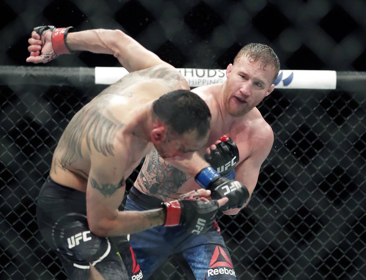 Tony Ferguson, izquierda, cae de espaldas tras recibir un puñetazo de Justin Gaethje durante u ...