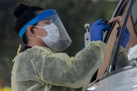 Un profesional médico de la UNLV realiza una prueba en la acera a un paciente que experimenta ...