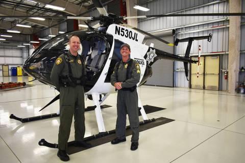 El oficial Ryan Petersen (izquierda) y el sargento Spencer Basner posan frente a un helicópter ...
