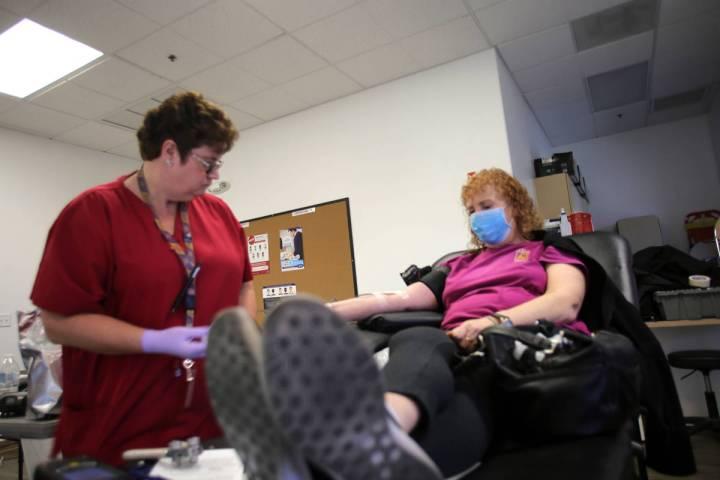 La flebotomista, Eva Clappa, izquierda, toma una donación de sangre de Susan Edwards durante u ...
