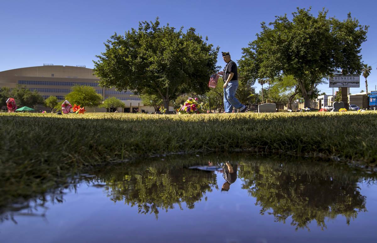 El veterano del Ejército, Howard Greenspon, se refleja en un pequeño charco de agua mientras ...