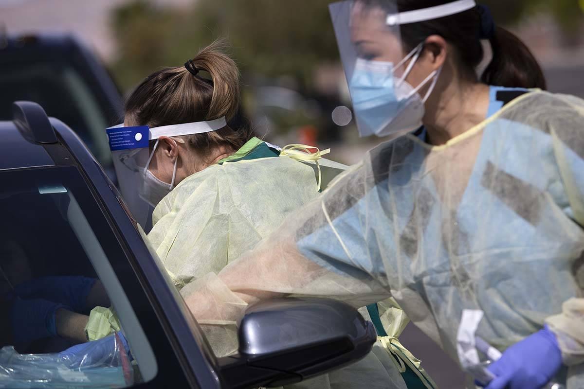 Una voluntaria toma la muestra de la nariz de un paciente en un sitio de pruebas de COVID-19 en ...