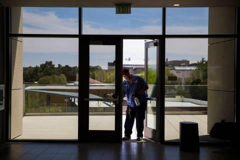 Robert Lucas, a la izquierda, un supervisor de custodia, desinfecta una puerta en el Salón de ...