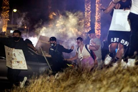 Manifestantes corren después de que la policía de Las Vegas disparara gas lacrimógeno y bala ...