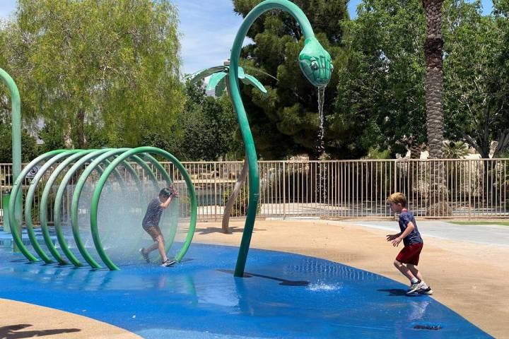 Dos niños corriendo a través de los rociadores en el Aliante Nature Discovery Park mientras s ...
