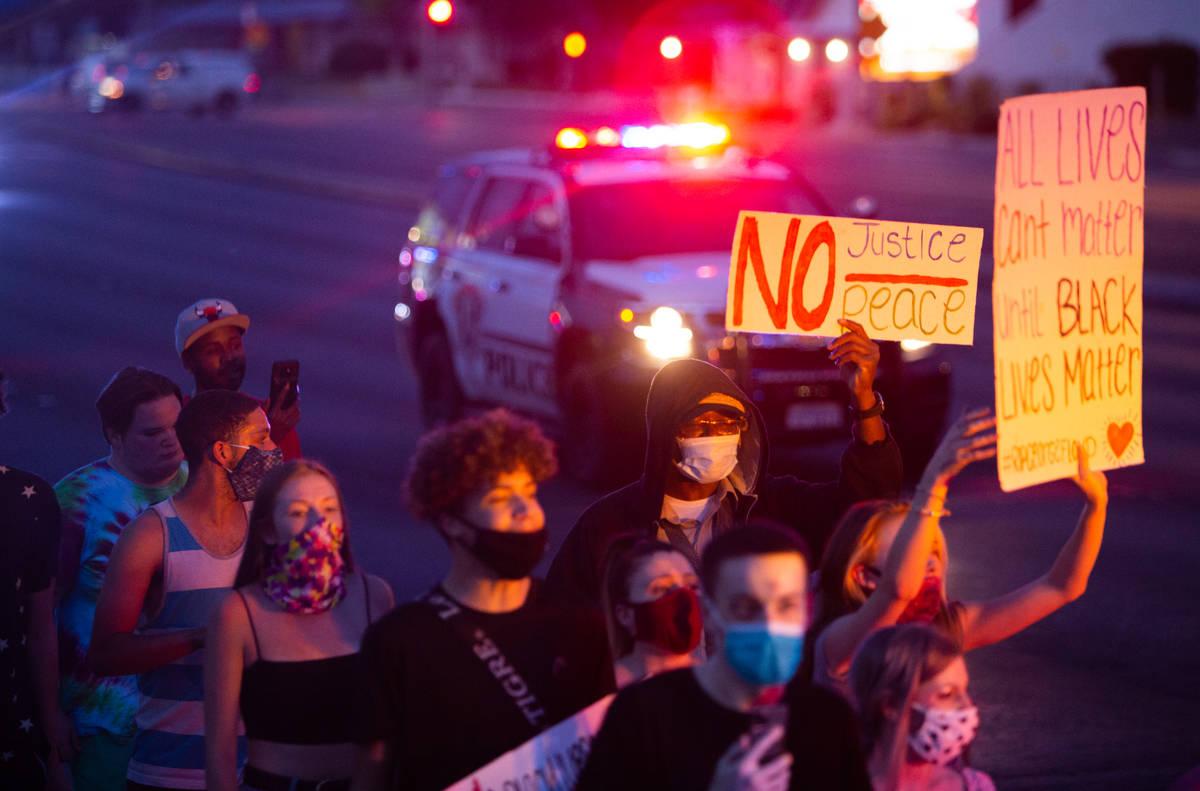 Manifestantes marchan mientras la policía los escolta durante una protesta de Black Lives Matt ...