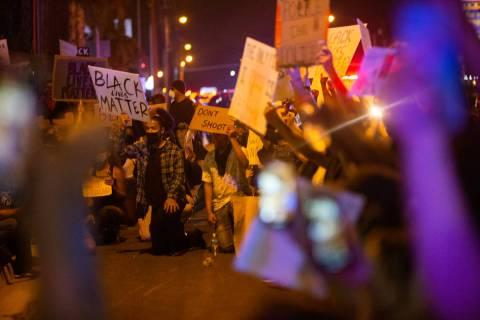 Manifestantes se arrodillan juntos antes de hacer un momento de silencio durante una protesta d ...
