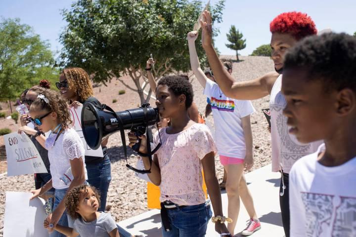 """Chasadity Patterson-Hudson, centro, de 11 años, toma el turno del megáfono para cantar """"sin j ..."""