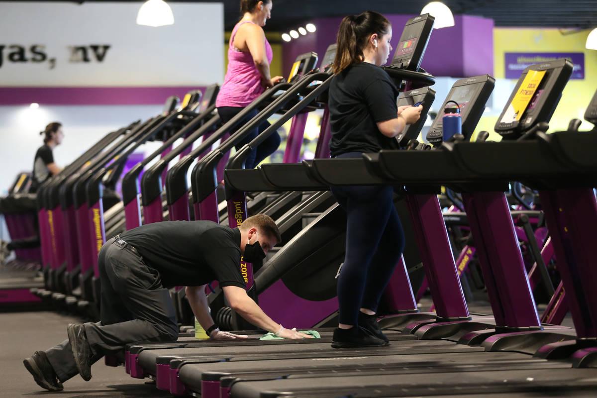 El gerente Hunter Jespersen limpia una caminadora en el gimnasio Planet Fitness de Las Vegas el ...