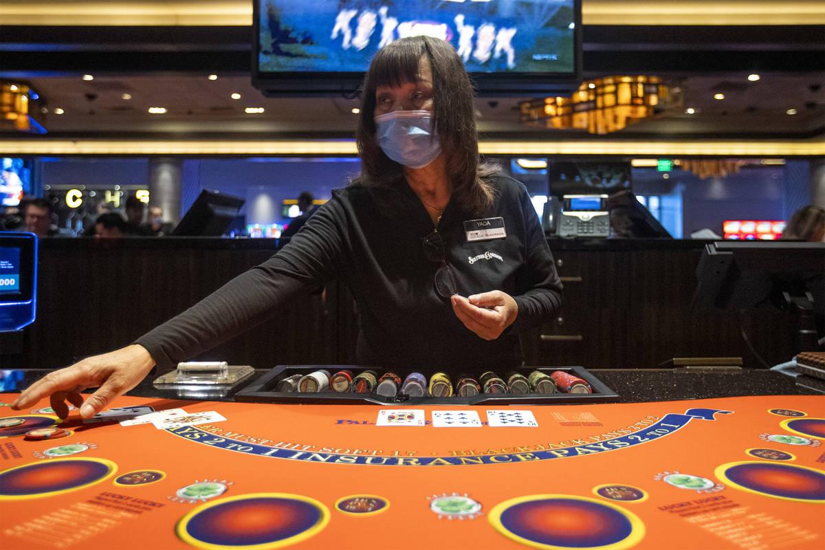 Una croupier de blackjack lleva un cubrebocas mientras reparte un juego en Palace Station, ya q ...