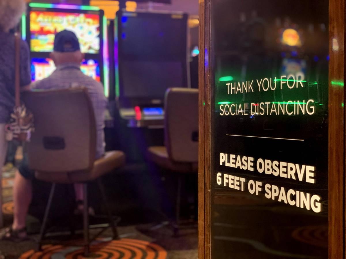 Un letrero que pide distanciamiento social se ve mientras los individuos juegan en el Casino Gi ...