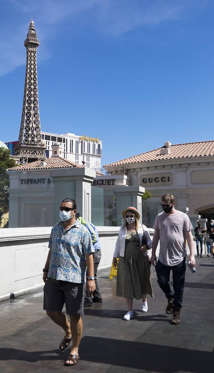 Visitantes cruzan un puente peatonal en el Strip de Las Vegas el domingo, 21 de junio de 2020. ...