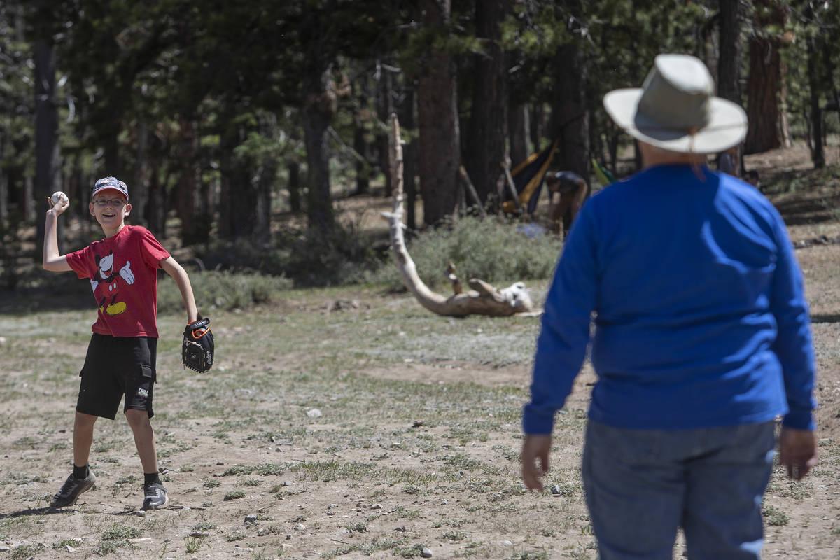 Landon Whitehead, de 12 años, juega a la pelota con su abuelo, Doug Whitehead, de 61 años, en ...