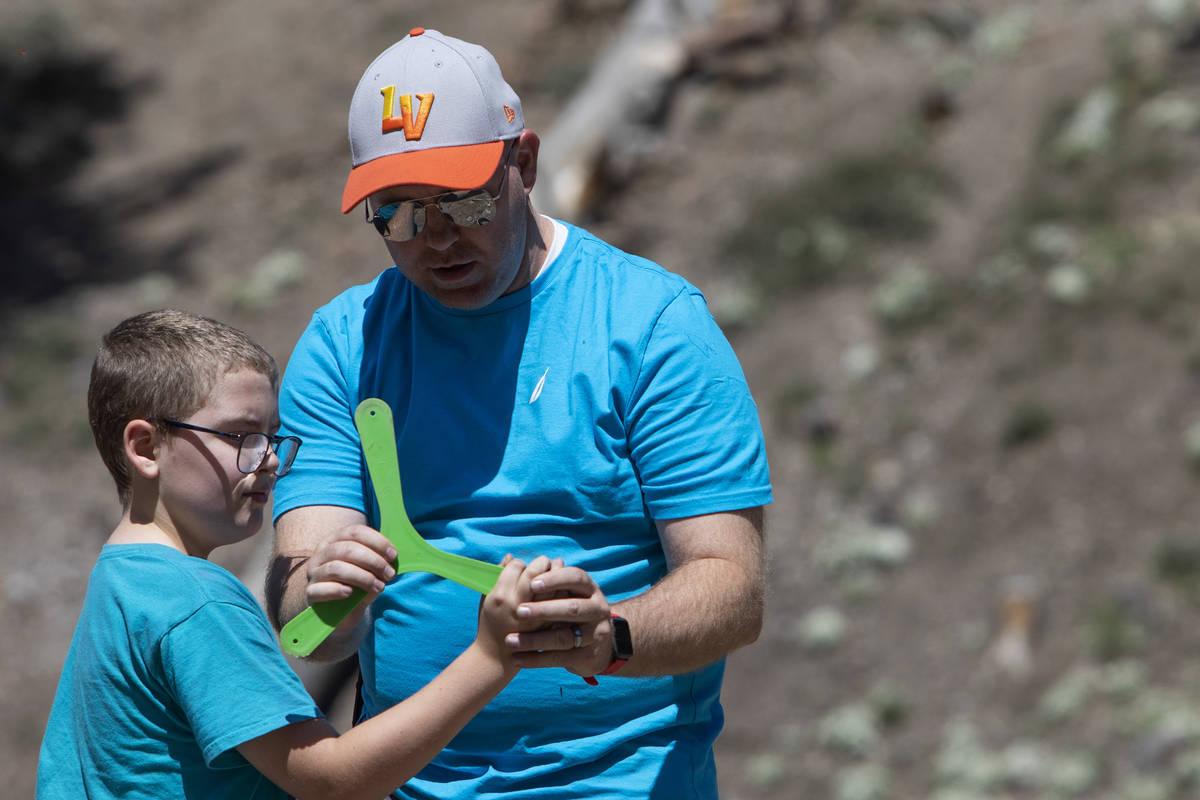 Jeff Whitehead enseña a su hijo, Garrett Whitehead, de 8 años, cómo lanzar un bumerán en el ...