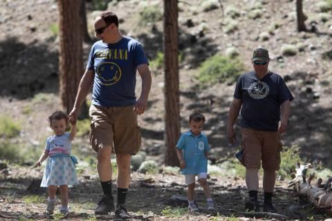 Thomas Doyle, izquierda, camina con su hija, Mia Doyle, de dos años, de vuelta a su campamento ...