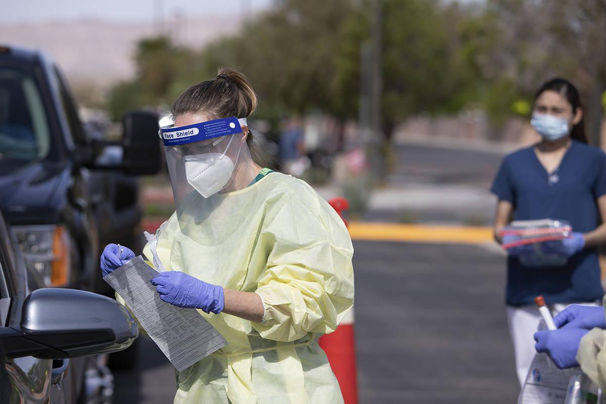 Una voluntaria se prepara para tomar una muestra de la nariz de un paciente como parte de la pr ...