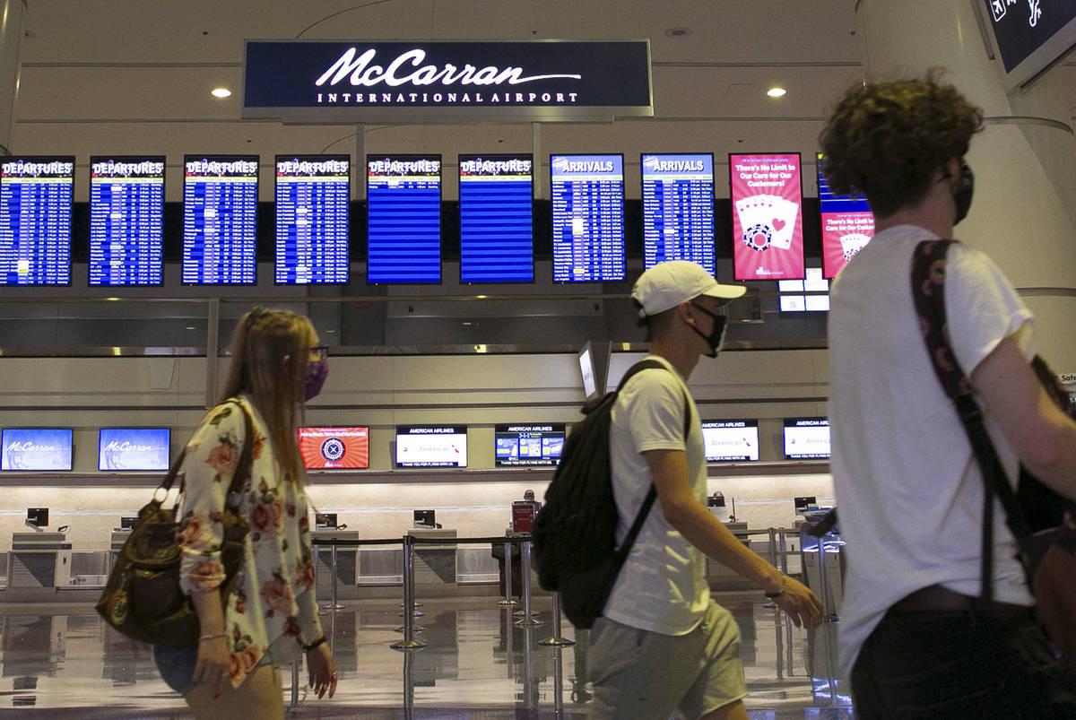 Pasajeros pasan por el letrero del Aeropuerto Internacional McCarran el miércoles, 24 de junio ...