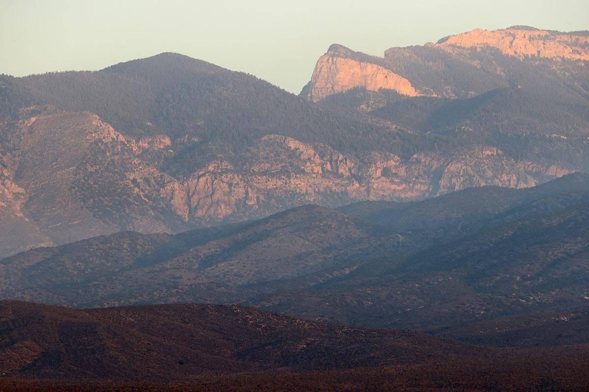El sol se eleva mientras las tripulaciones luchan contra el incendio de caoba en el Monte Charl ...