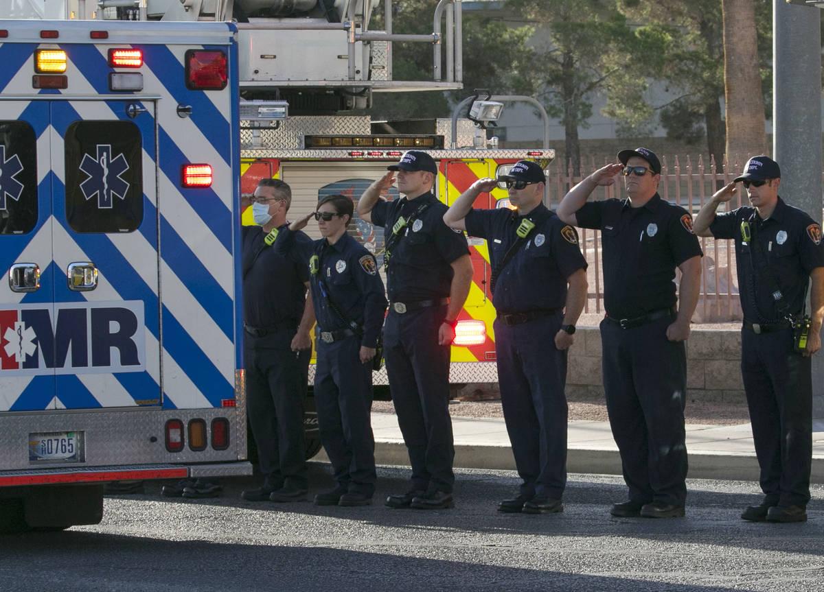 Bomberos del Condado Clark saludan durante una procesión mientras una ambulancia que lleva al ...