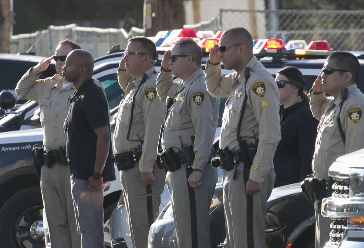 Oficiales de policía de Las Vegas saludan durante una procesión en la que una ambulancia que ...