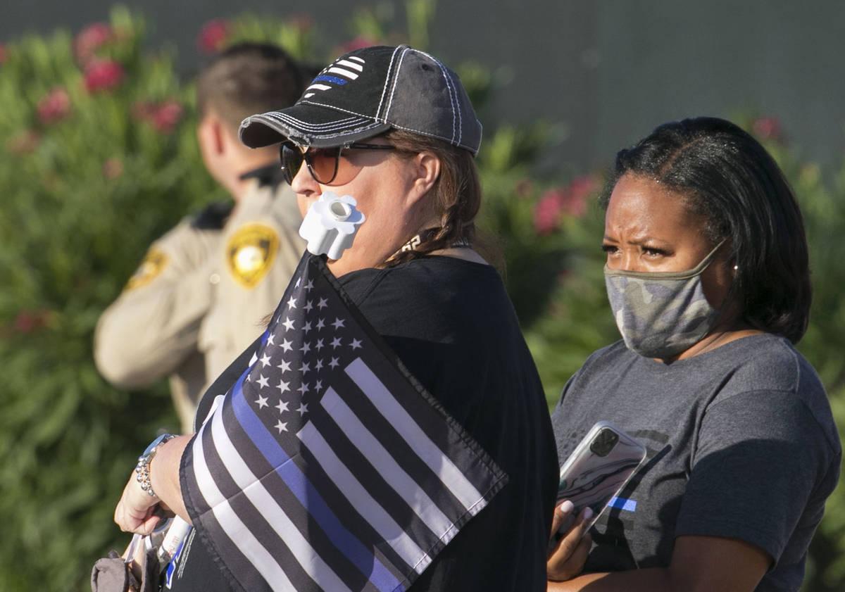 Cindy Novak, derecha, observa una procesión mientras una ambulancia que lleva al oficial de po ...