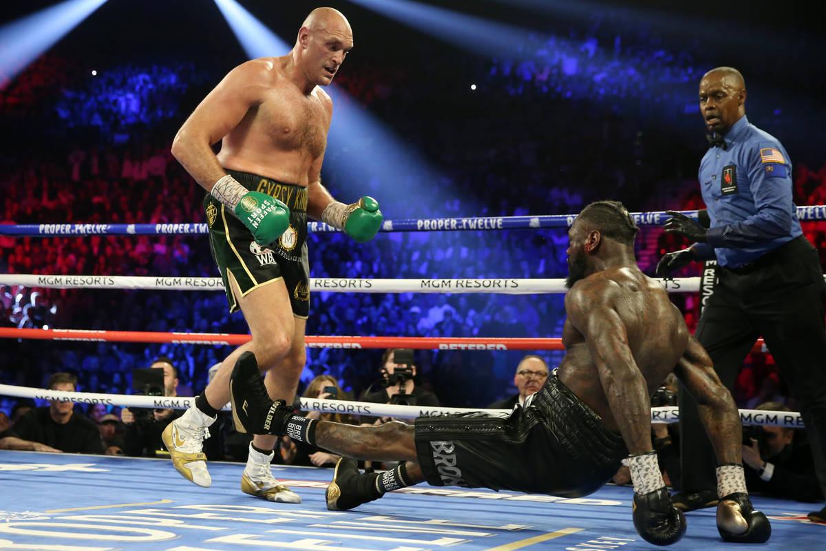 Tyson Fury, derecha, derriba con un golpe a Deontay Wilder en el quinto asalto durante su pelea ...