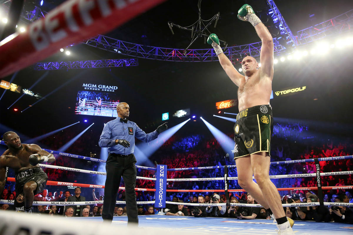 Tyson Fury, derecha, levanta sus manos después de derribar a Deontay Wilder en el tercer asalt ...